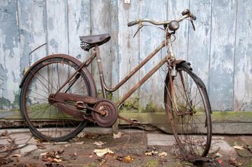 Verrostetes altes Fahrrad lehnt an einer Holzwand