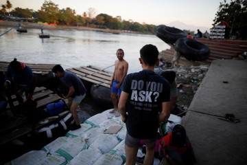 People belonging to a caravan of migrants from Honduras en route to the United States, cross the Suchiate river to Mexico from Tecun Uman