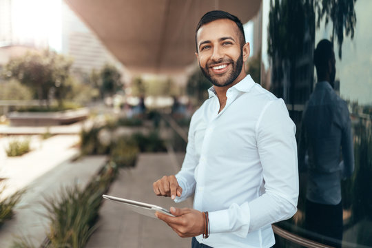 Portrait of a young confident smiling indian man holding a tablet and looking into the distance