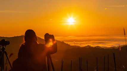 silhouette landscape at morning time tourist take pictures of the sunrise and mist on the mountain