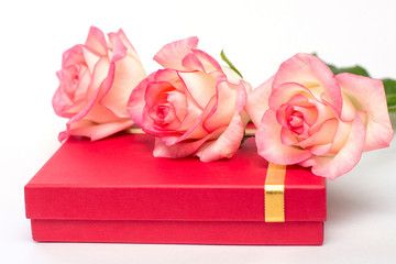 Three roses lie on the red bass box. Gifts on a white background. A gift for the beloved.