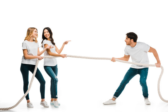 smiling young women and concentrated man pulling rope isolated on white