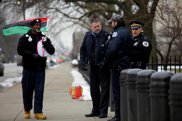 A protester walks past Chicago police officers during the sentencing for Jason Van Dyke for the fatal shooting of Laquan McDonald at the Leighton Criminal Courts Building in Chicago