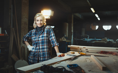 Beautiful middle aged woman worker posing against background of a woodworking workshop. Concept of motivated women, gender equality, image of femininity in modern world