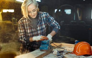 Active Middle aged woman selects wood in workshop. Concept of professionally oriented motivated modern woman. Gender equality, image of femininity
