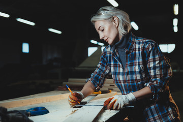 Beautiful middle aged woman carpenter designer works with ruler, make notches on the tree in workshop.  Image of modern femininity. Concept of professionally motivated women