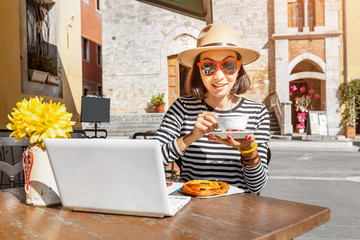 Happy asian freelancer woman ic casual clothes working with laptop pc in outdoors cafe