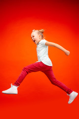 Young happy caucasian teen girl jumping in the air, isolated on red studio background. Beautiful female full length portrait. Human emotions, facial expression concept.