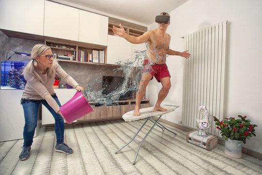 marito gioca a fare il surfer sull'asse da stiro e la moglie gli tira una secchiata d'acqua
