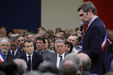 French President Emmanuel Macron listens to Mayor of Cahors Jean-Marc Vayssouze-Faure during a meeting attended by some 600 mayors of Occitania to relay their constituent's grievances, in Souillac