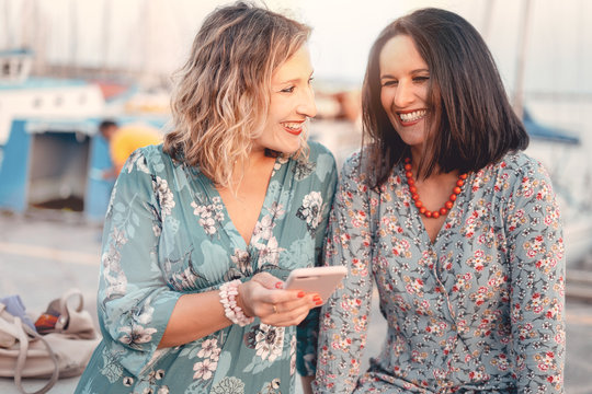 Two women friends laughing while watching the smartphone screen