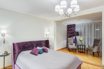 Interior of stylish bedroom in gray, violet, white colors and wallpapers with animals pattern, Big cozy bed with velor headboard and pillows. Flower on table and two armchair around. So lighting room.