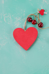 Valentine's Day, surprise gift with red Cherry. Healthy food.Red berry cherries,wooden heart. SUMMER love, Still life on pastel background. Flat lay, Top view. Copy space. love of cherry. Romantic