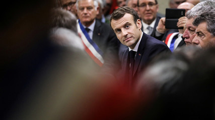 French President Emmanuel Macron looks on during a meeting attended by some 600 mayors of Occitania to relay their constituent's grievances, in Souillac