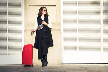 Pretty young woman standing with suitcase while waiting her train in the street.