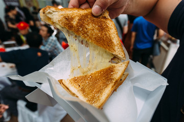 Pulling separate a Grilled Cheese Toast by hand with stretching cheese inside.