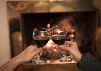 Close up of happy couple drinking wine by fire place celebrating love and winter holidays vacation