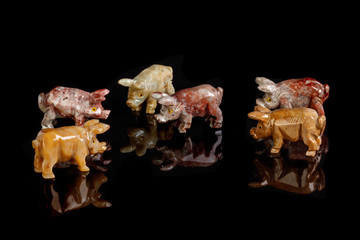 Pig figurines made of onyx, jasper, glass, gold on a black background
