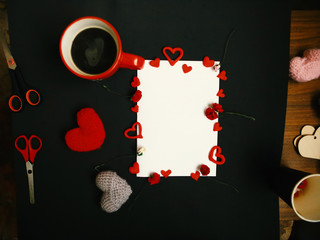 Flat lay photo with cup of coffee, handmade knitted hearts and white mockup blank. Valentines Day greeting card