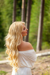 Young beautiful blonde woman in white pegnoir underwear posing in forest in summer