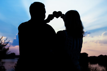 happy couple silhouette on the sunset background nature