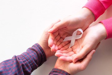 man and woman hold white ribbon close up