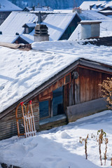 House in Gstaad (Switzerland) and a sleigh with snow in winter