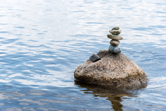 small stones balanced on boulder in the water