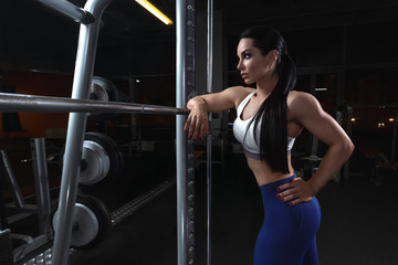Pretty young brunette woman is relaxing near barbell in dark gym
