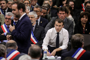 French President Emmanuel Macron takes notes during a meeting attended by some 600 mayors of Occitania to relay their constituent's grievances in Souillac