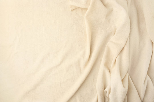 Abstract beige woven textile drape background. Waving cloth fabric canvas.