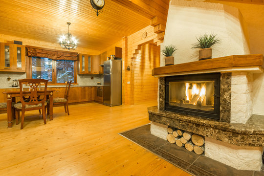 Fireplace with burning fire. Warm home interior of wooden house