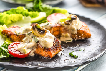 Delicious grilled roasted salmon fillets or steaks with mushroom sauce sesame tomatoes and lettuce salad