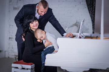 the child plays the piano for mom and dad