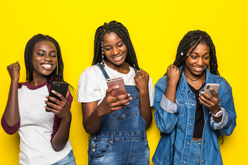 Portrait of three happy young african woman friends smiling while using mobile phone together with win gesture isolated on yellow background