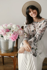Beautiful brunette boho girl in hat smiling with big peonies bouquet. Stylish hipster woman sitting at metal bucket with peonies on rustic wooden chair. International Womens Day