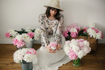 Boho girl sitting at pink and white peonies in rustic basket and metal bucket on wooden floor. Stylish hipster woman in bohemian dress holding pink peony among flowers. Countryside living