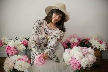 Happy boho girl smiling at pink and white peonies on rustic wooden floor. Stylish hipster woman in hat and bohemian floral dress  with flowers. International Womens Day. Countryside living