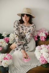 Portrait of boho girl sitting at pink and white peonies on rustic wooden floor. Stylish hipster woman in bohemian dress holding pink peony among flowers. International Womens Day