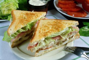 Plato con un sandwitch con pan de molde tostado, lechuga, tomate, jamón cocido y queso.
