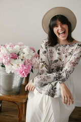 Stylish boho girl in hat sitting and laughing at metal bucket with peonies on rustic wooden chair. Beautiful hipster woman posing with big peonies bouquet. Countryside living.