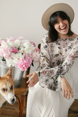 Stylish boho girl sitting at metal bucket with peonies on rustic wooden chair and playing with cute golden dog.Beautiful hipster woman playing with her pet at big peonies bouquet.