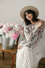 Beautiful brunette boho girl in hat posing with big peonies bouquet. Stylish hipster woman sitting at metal bucket with peonies on rustic wooden chair. International Womens Day