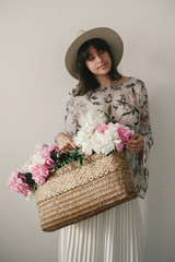 Boho girl in hat holding pink and white peonies in rustic basket. Stylish hipster woman in bohemian floral dress posing with flowers. International Womens Day. Countryside living