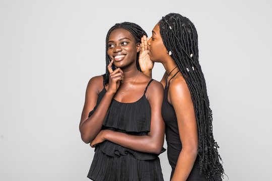 Portrait of two happy young african women sharing secrets isolated on gray background