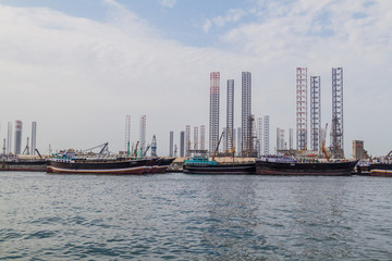 Boats, oil derricks and cranes in the Khalid port in Sharjah, United Arab Emirates.
