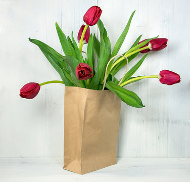 red tulips in generic brown paper bag on rustic whitewashed wood