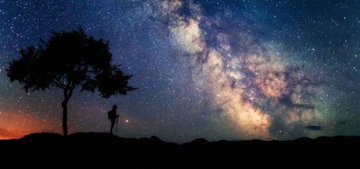 Woman under tree looking at the stars and Milky Way. Scenery landscape with night starry sky and silhouette of standing woman. Milky Way Galaxy with traveler. Universe.