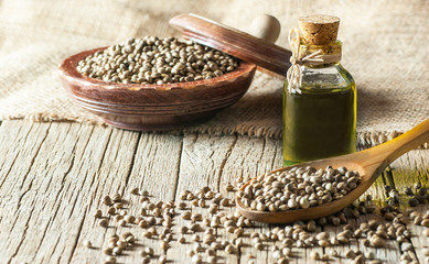 Heap of dried organic hemp seeds or cannabis plant seeds in spoon and bowl with glass of hemp seed oil on wooden backdrop. cannabis herb concept. hemp seed used birdseed