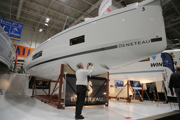 A man takes a picture with his phone of a Beneteau yacht at the Toronto Boat Show